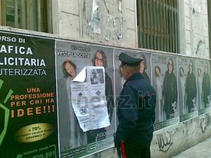 Un carabiniere davanti al manifesto